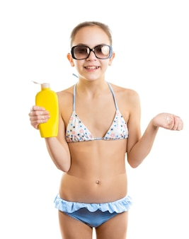 Happy smiling girl in sunglasses holding bottle of suntan lotion