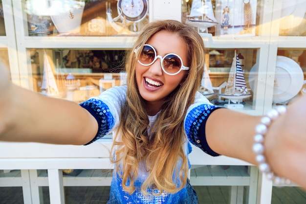 Selfie、明るいスタイリッシュなセーターとサングラスのお土産ウィンドウショッピングに近いポーズ笑う女性の面白い遊び心のあるイメージを取って幸せな笑顔の女の子。