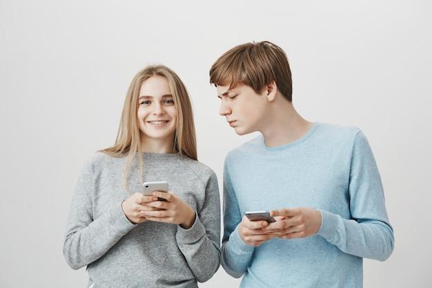 Счастливая усмехаясь девушка используя мобильный телефон, парень смотря серьезный на ее дисплее смартфона
