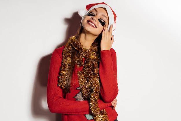 패치의 눈 아래 새해를 기다리는 산타클로스 같은 빨간 모자를 쓴 행복한 웃는 소녀