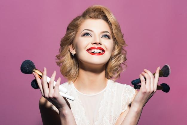 우아한 makeupholding 메이크업 브러쉬와 함께 행복 하 게 웃는 소녀.