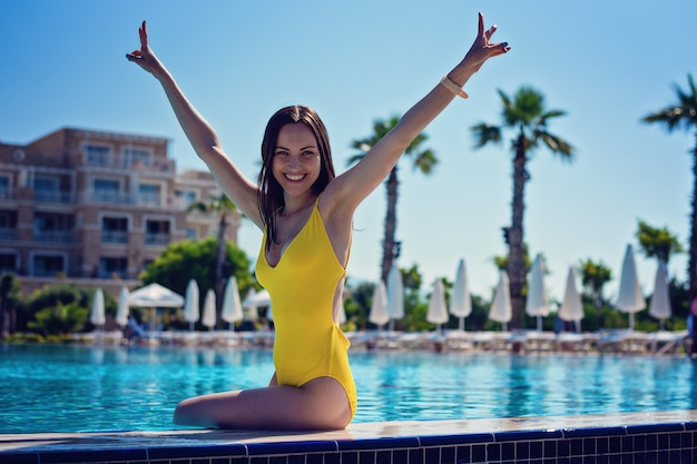 Happy smiling girl with her hands high sitting in a yellow swimsuit on the edge of the pool on vacation