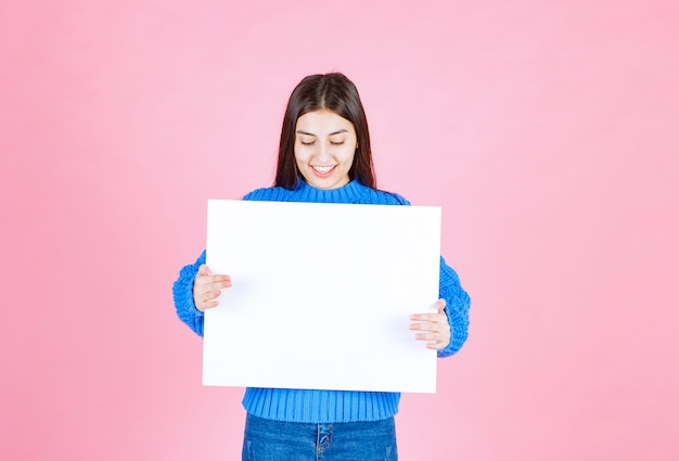 Happy smiling girl with white blank board.