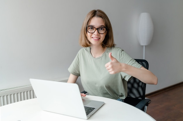 Happy smiling girl working online or studying and learning while using notebook showing thumb up. freelance work concept