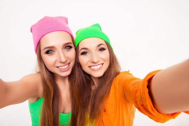 Счастливые улыбающиеся девушки в цветных шляпах, делающие селфи