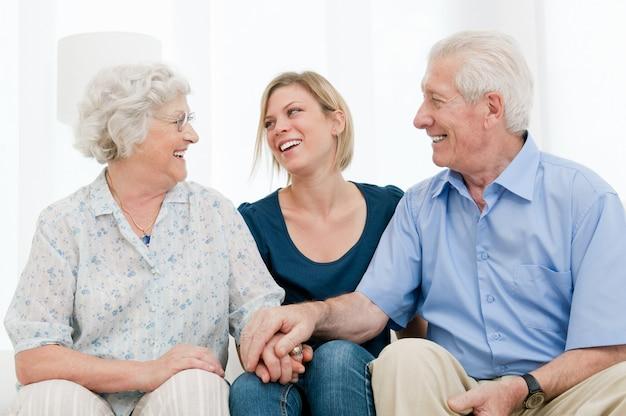 Счастливая улыбающаяся внучка с бабушкой и дедушкой дома