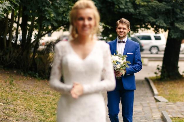 Счастливый улыбающийся жених идет с приятным свадебным букетом невесты