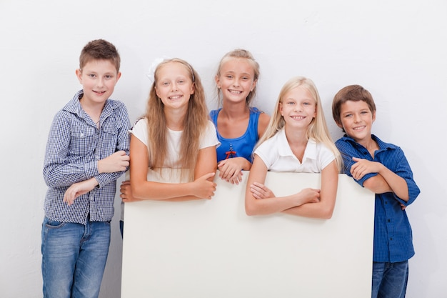 Happy smiling group of kids, boys and girls, showing board