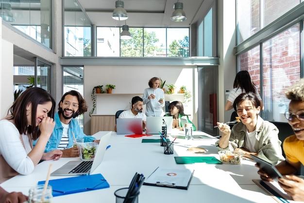 多民族の同僚の幸せな笑顔のグループが一緒に昼休みを持っていますコピースペースビジネス