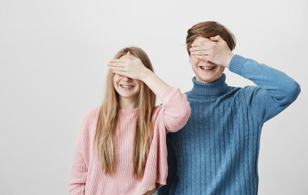 Счастливый улыбающийся парень и девушка с брекетами закрывают глаза ладонями