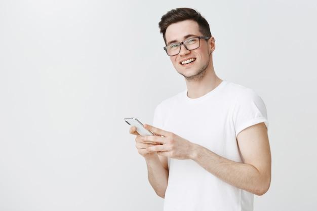 Ragazzo sorridente felice in bicchieri utilizzando il telefono cellulare e alla ricerca