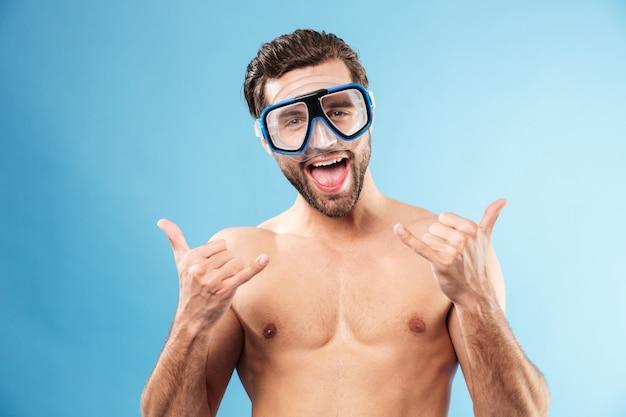 Счастливый улыбающийся парень в плавательных очках показывает палец вверх жест