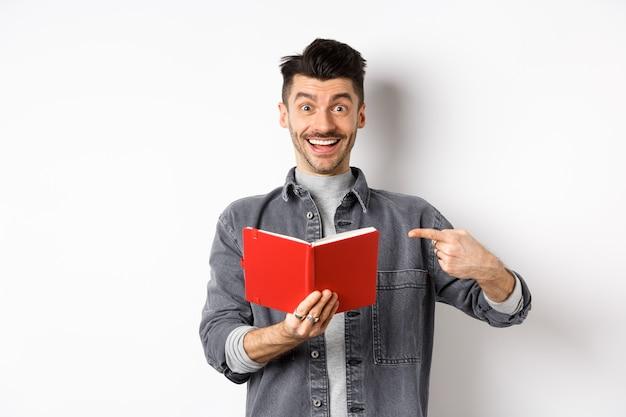 빨간색 플래너를 가르키고, 좋은 저널이나 책, 흰색 배경에 서있는 행복 웃는 남자.