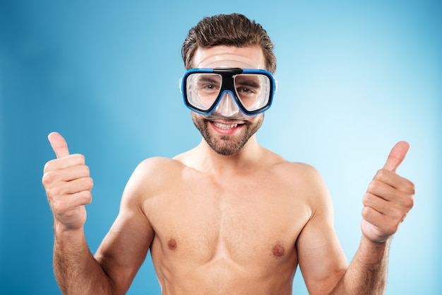 Happy smiling guy in swimming goggles showing thumbs up gesture