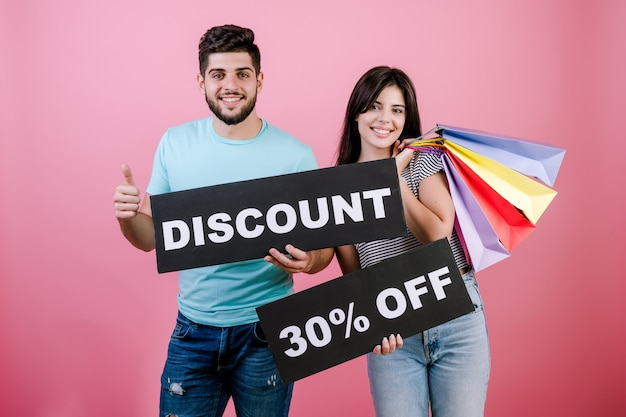 Happy smiling handsome couple man and woman with discount 30% off sign and colorful shopping bags
