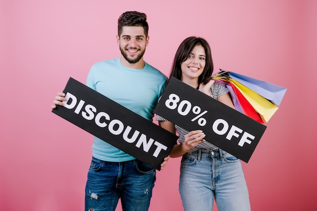 Happy smiling handsome couple man and woman with discount 90% off sign and colorful shopping bags