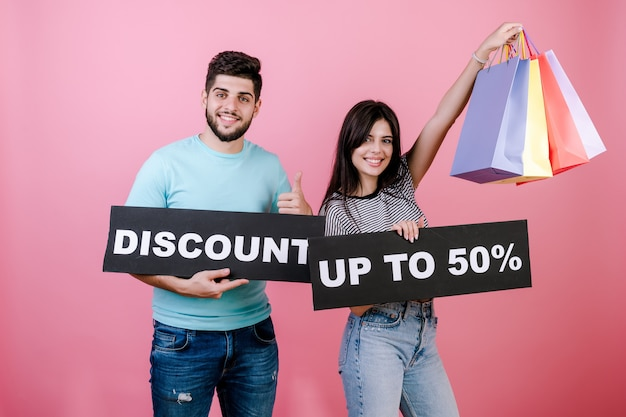 Happy smiling handsome couple man and woman with discount up to 50% sign and colorful shopping bags