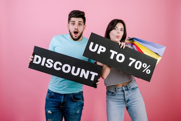 Happy smiling handsome couple man and woman with discount up to 70% sign and colorful shopping bags