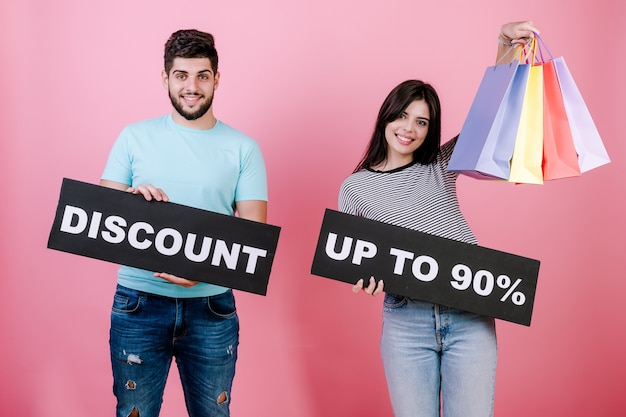 Happy smiling handsome couple man and woman with discount up to 90% sign and colorful shopping bags
