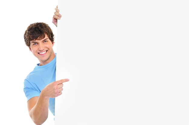 Happy smiling handsome  man look out from  banner and indicate by finger on it