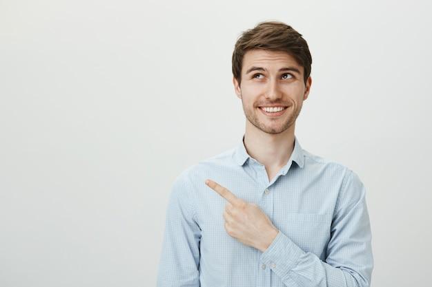 幸せな笑顔のハンサムな男を探して、バナーで左上隅を指す