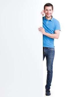 Il giovane bello sorridente felice osserva fuori dall'insegna in bianco - isolato su bianco.