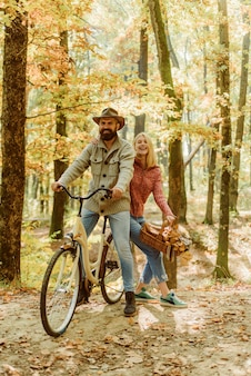 Happy smiling hipster couple on cycle ride in autumnal sunny forest bearded handsome man in hat and ...