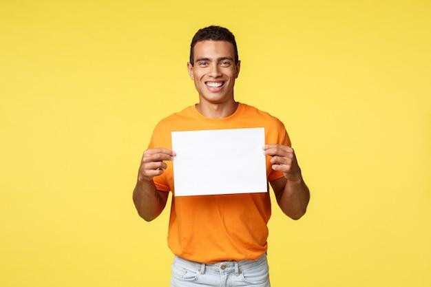 Счастливый улыбающийся латиноамериканский мужчина в оранжевой футболке, держа бумагу над грудью и ухмыляясь, как дать совет, написать любимый продукт или веб-сайт магазина, дать совет, порекомендовать место для покупок,