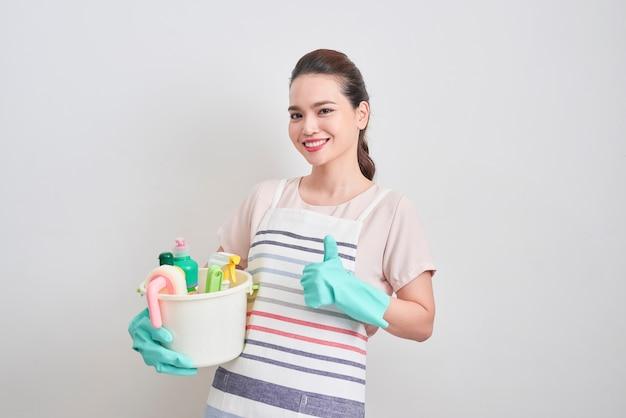 幸せな笑顔の主婦は、掃除道具を押しながら、白い背景で隔離の親指を現しています。クリーニング サービス、ハウスキーピング コンセプト