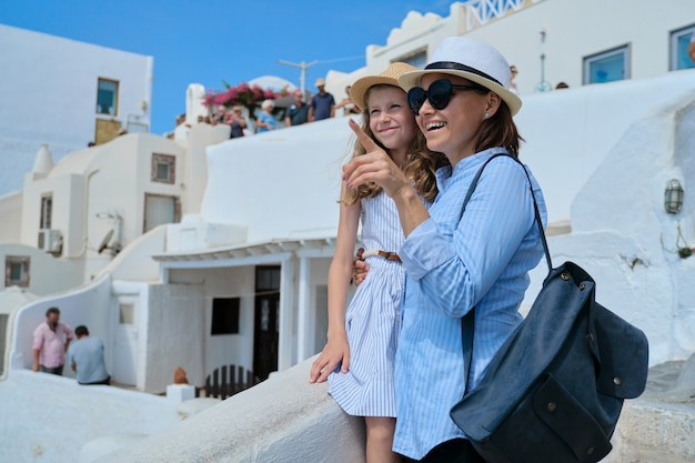 Happy smiling hugging mother and child daughter enjoying scenic views of nature and architecture of santorini island. summer holidays with family