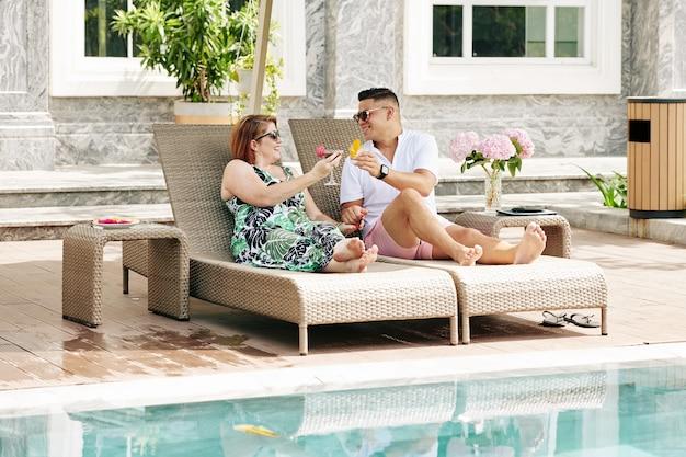 Счастливые улыбающиеся муж и жена поджаривают бокалы вкусных освежающих коктейлей, отдыхая в шезлонгах