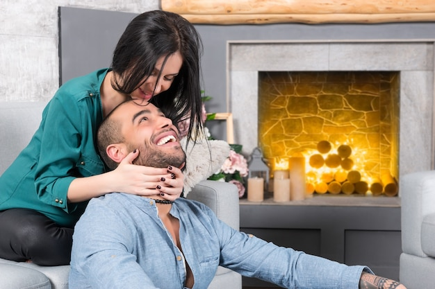 Happy smiling international couple of man with beard and his brunette pregnant wife sitting on the sofa and hugging him in the living room with a fireplace