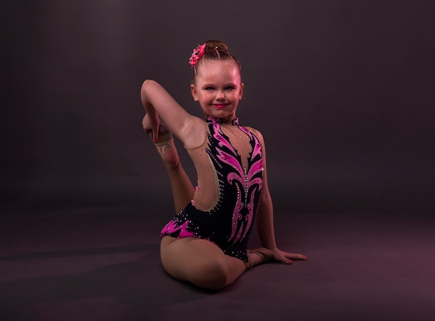 Happy smiling ittle girl in gymnast in costume sitting in position in studio, trying to do circle with leg and arm.