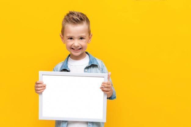 Счастливый улыбающийся ребенок держит белую рамку с копией пространства для текста сертификата или диплома