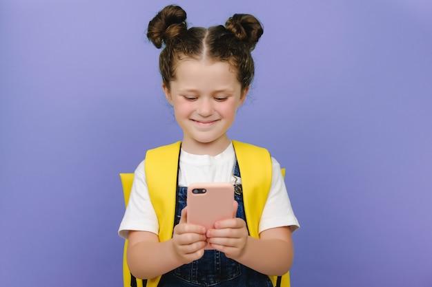 전화를 들고, 화면을 보고, 보라색 배경 벽 위에 고립되어 서 있는 행복한 미소 짓는 여고생. 휴대폰에서 모바일 앱을 사용하여 노란색 배낭을 메고 웃고 있는 아름다운 여학생