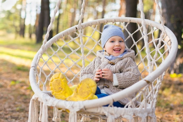 Счастливый улыбающийся малыш качается в подвесном кресле в лесу