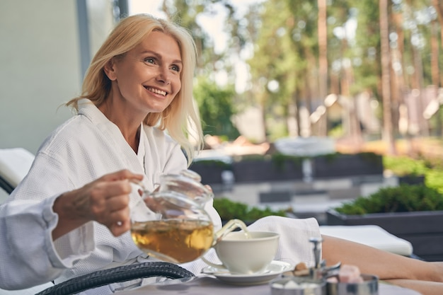 책상에 흰색 컵에 차를 포링하는 동안 손에 주전자를 들고 행복 웃는 아가씨