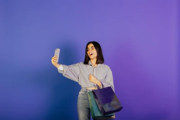 青いシャツとジーンズの幸せな笑顔の女性は、ギフトバッグを保持し、自分撮りを取ります。