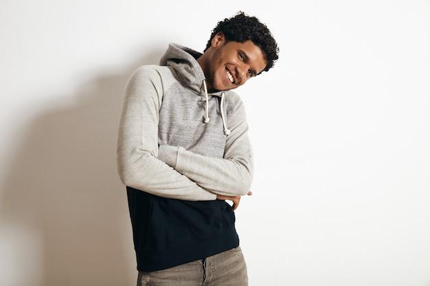 幸せな笑顔のラテン系の男は、フードと苦しめられたジーンズで空白の灰色の黒いセーターを着て、胸に手を交差させ、白で隔離