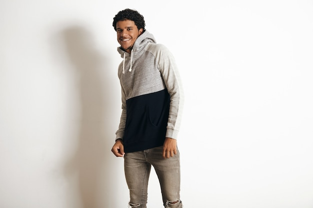 Happy smiling latino guy wears blank grey black sweater with hood and distressed jeans, isolated on white