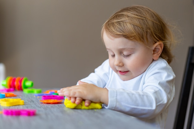 Happy smiling little boy playing with colorful clay alone. child using plasticine and playing dough.