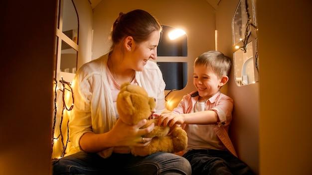 Счастливый улыбающийся маленький мальчик с молодой матерью, играя с игрушечным мишкой в палатке или игрушечном домике ночью. понятие о детской игре и семье, проводящей время вместе в ночное время.
