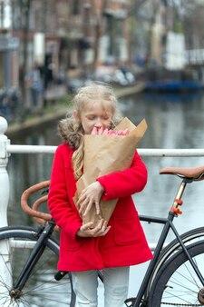 Счастливая улыбающаяся маленькая девочка, держащая букет тюльпанов, стоящая на улице амстердама. нидерланды
