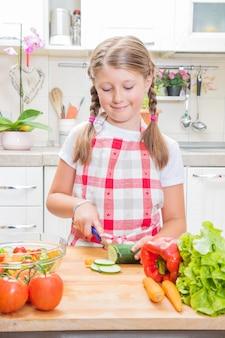 행복 하 게 웃는 어린 소녀 집에서 부엌에서 야채를 절단