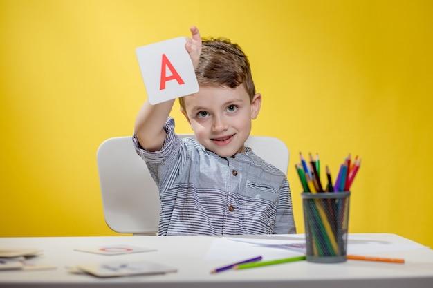 행복 미소 작은 유치원 소년 학교가 시작하기 전에 아침에 숙제를 집에서 편지를 보여줍니다