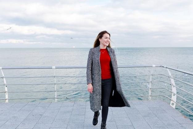 Donna dai capelli lunghi sorridente felice con grandi occhi azzurri in camicia rossa e cappotto grigio cammina vicino al mare
