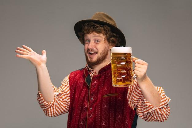 灰色のスタジオの背景に分離されたジェスチャーで伝統的なオーストリアまたはバイエルンの衣装に身を包んだ幸せな笑顔の男