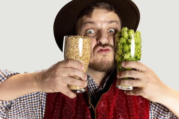 お祝いの食べ物と赤い背景で隔離のビールとテーブルに座っている伝統的なオーストリアまたはバイエルンの衣装に身を包んだ幸せな笑顔の男