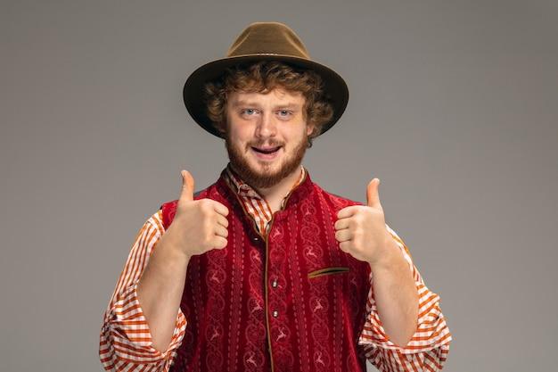 Счастливый улыбающийся человек, одетый в традиционный австрийский или баварский костюм