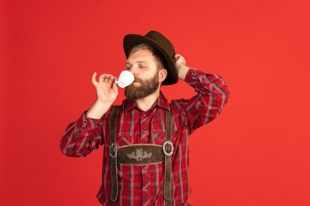 お祝いの食べ物と伝統的なバイエルンの衣装に身を包んだ幸せな笑顔の男。お祝い、オクトーバーフェスト、フェスティバルのコンセプト。広告用のコピースペース